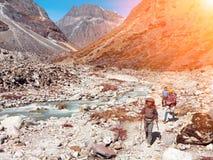 Gruppo di viandanti che camminano in montagne lungo il fiume selvaggio della montagna Immagini Stock