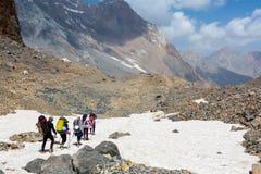 Gruppo di viandanti che camminano sul campo di neve Fotografia Stock