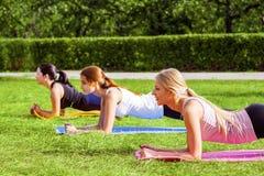 Gruppo di vista laterale di belle giovani donne viscose in buona salute soddisfatte che fanno i exersices sull'erba verde nel par fotografia stock