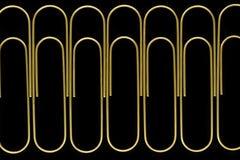 Gruppo di vista tagliente e chiara dei paperclips dorati che stanno nella linea sulla superficie nera del fondo fotografia stock libera da diritti
