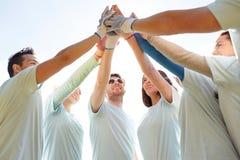Gruppo di volontari che fanno livello cinque all'aperto immagine stock