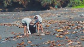 Gruppo di volontari che puliscono spiaggia Il volontario alza e getta i rifiuti di plastica nella borsa ambientale archivi video