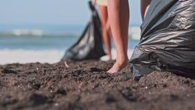 Gruppo di volontari che puliscono spiaggia Il volontario alza e getta una bottiglia di plastica nella borsa Offerta e archivi video
