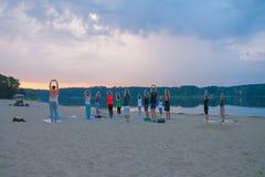 gruppo di yoga di pratica dei giovani durante l'alba fotografia stock
