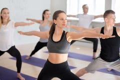 Gruppo di yoga di pratica della gente sportiva, facente posa del guerriero 2 fotografia stock libera da diritti