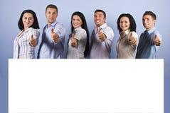 Gruppo felice con la bandiera ed i pollici in bianco in su
