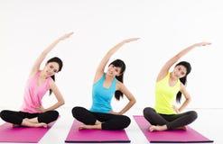 Gruppo felice della giovane donna che fa gli esercizi di yoga Immagine Stock