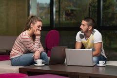 Gruppo felice di adolescenti al caffè facendo uso del computer portatile Fotografia Stock Libera da Diritti