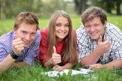 Gruppo felice di allievi con i pollici in su Fotografia Stock