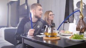 Gruppo felice di amici che chiacchierano mangiando il tè delle bevande in caffetteria e fumando narghilé archivi video