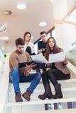 Gruppo felice di amici che si siedono sulle scale nella scuola Fotografia Stock