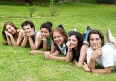 Gruppo felice di amici che sorridono in una sosta Fotografia Stock
