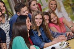 Gruppo felice di anni dell'adolescenza a scuola immagine stock