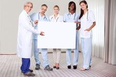 Gruppo felice di medici che tengono un cartello in bianco Fotografia Stock
