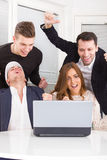 Gruppo felice emozionante di amici che vincono online facendo uso del computer portatile Fotografia Stock