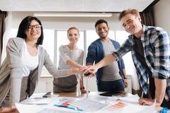Gruppo felice positivo degli ingegneri che si tengono per mano insieme Fotografie Stock