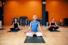 Gruppo femminile con l'istruttore che si siede nella posa di yoga Fotografia Stock Libera da Diritti