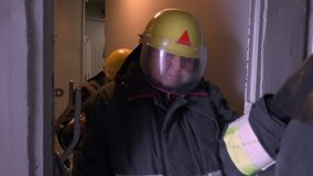 Gruppo femminile dei soccorritori in uniforme protettiva e dei caschi che vanno in tunnel dentro costruzione Addestramento femmin video d archivio