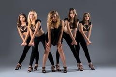 Gruppo femminile di ballo che posa nei reggiseni neri artistici Immagini Stock