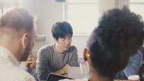 Gruppo misto di etnia che discute le idee di affari Giovane impiegato asiatico che parla al meetup di 'brainstorming' di lavoro d stock footage