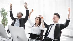 Gruppo molto felice di affari che si siede allo scrittorio immagini stock libere da diritti