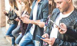 Gruppo multiculturale degli amici facendo uso dello smartphone all'università fotografie stock