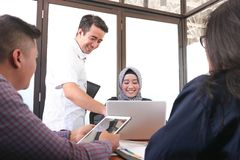 Gruppo multietnico di gente di affari felice che collabora con il computer portatile e la compressa fotografia stock libera da diritti