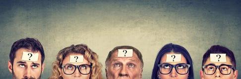 Gruppo multietnico di gente di pensiero con cercare del punto interrogativo