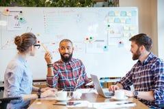 Gruppo multietnico di giovani che confrontano le idee sulla riunione d'affari immagini stock