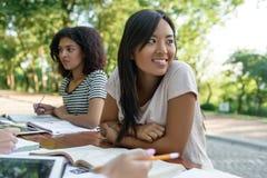 Gruppo multietnico di giovani studenti che si siedono e che studiano Fotografia Stock