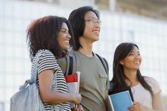 Gruppo multietnico di giovani studenti sorridenti che stanno e che parlano Fotografia Stock