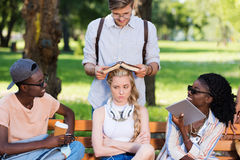 Gruppo multietnico di studenti che si siedono insieme sul banco in parco Fotografie Stock Libere da Diritti