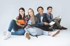 gruppo multietnico di studenti sorridenti con i taccuini ed i dispositivi digitali fotografia stock