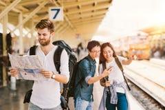 Gruppo multietnico di viaggiatori dello zaino che usando navigazione dello smartphone e della mappa alla stazione ferroviaria, co Fotografie Stock Libere da Diritti