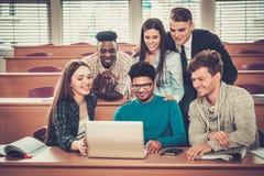 Gruppo multinazionale di studenti allegri che prendono una parte attiva in una lezione mentre sedendosi in una conferenza corrido Immagini Stock