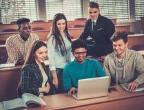 Gruppo multinazionale di studenti allegri che prendono una parte attiva in una lezione mentre sedendosi in una conferenza corrido Fotografie Stock Libere da Diritti