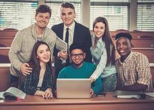Gruppo multinazionale di studenti allegri che prendono una parte attiva in una lezione mentre sedendosi in una conferenza corrido Fotografia Stock Libera da Diritti