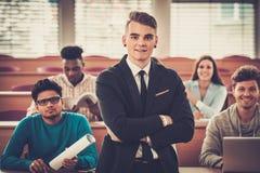 Gruppo multinazionale di studenti allegri che prendono una parte attiva in una lezione mentre sedendosi in una conferenza corrido Immagini Stock Libere da Diritti