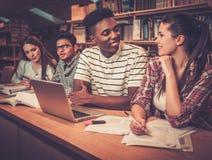 Gruppo multinazionale di studenti allegri che studiano nella biblioteca universitaria Fotografie Stock