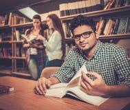 Gruppo multinazionale di studenti allegri che studiano nella biblioteca universitaria Immagine Stock Libera da Diritti