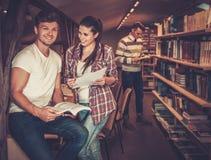 Gruppo multinazionale di studenti allegri che studiano nella biblioteca universitaria Fotografia Stock