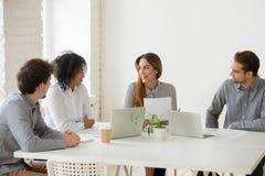 Gruppo multirazziale che discute il contratto di lavoro nello spazio coworking fotografia stock libera da diritti