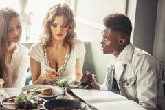 Gruppo multirazziale di amici pranzando insieme Due donne europee ed un tipo africano al caffè Fotografia Stock