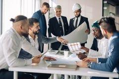 Gruppo multirazziale di costruttori e di architetti che discutono modello all'ufficio immagini stock