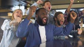 Gruppo multirazziale di fan che sostiene sport di squadra, scopo di conquista d'esultanza, vittoria video d archivio