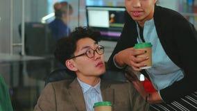 Gruppo multirazziale di gente di affari che chiacchiera e che beve caffè archivi video