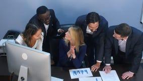 Gruppo multirazziale di gente di affari allegra che discute infographics analitico mentre avendo un cervello che infuria in Fotografia Stock Libera da Diritti