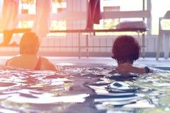 Gruppo o giovani e senior nell'esercitazione aquarobic della piscina di forma fisica Immagine Stock