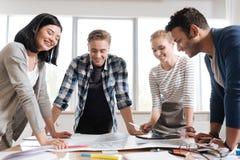 Gruppo piacevole piacevole degli ingegneri che discutono il loro progetto fotografia stock libera da diritti