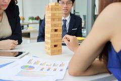 Gruppo premuroso e conscio di gente di affari che gioca la torre di legno del blocco in ufficio Concetto di affari di strategia e fotografie stock